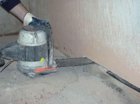 Przecinanie ściany maszyną wyposażoną w piłę łańcuchową w celu wykonania odcinkowej izolacji muru